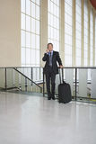 Businessman Using Cellphone In Airport Stock Photo