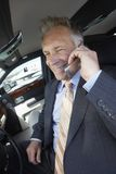 Businessman Using Cellphone In Car. Happy senior businessman using cellphone in car with airplane in the background Stock Photo