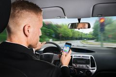 Businessman using cellphone while driving a car Royalty Free Stock Photo