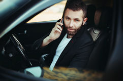 Businessman using a cellphone in his car. Handsome man sitting in car, talking on cellphone Stock Photos