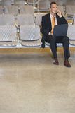 Businessman Using Cellphone And Laptop In Lobby Stock Photo