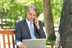 Businessman using cellphone and laptop in park Royalty Free Stock Photo