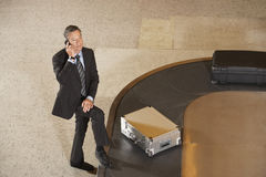 Businessman Using Cellphone By Luggage On Carousel In Airport Stock Image