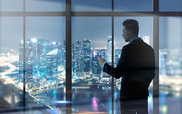 Businessman using cellphone. Side view of young businessman using cellphone against panoramic window with illuminated night city view Stock Photo