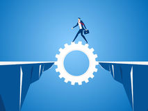 Businessman using cog gear to cross through the gap between hill.  Business risk and success concept. Stock Image