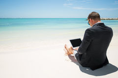 Businessman using computer on the beach Stock Image