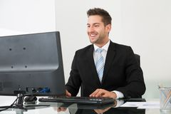Businessman using computer at desk Stock Image