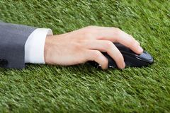 Businessman using computer mouse on grass Royalty Free Stock Images