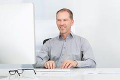 Businessman Using Computer. Portrait Of Mature Businessman Using Computer At Desk Royalty Free Stock Photography