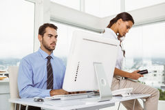 Businessman using computer while woman on call Stock Image