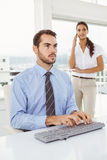 Businessman using computer while woman on call Stock Photography