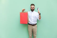 Businessman using credit card for online shopping. Looking at camera and toothy smile. Royalty Free Stock Photography