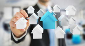 Businessman using 3D rendered small white and blue houses. Businessman on blurred background using 3D rendered small white and blue houses Stock Images