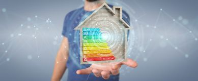 Businessman using 3D rendering energy rating chart in a wooden h. Businessman on blurred background using 3D rendering energy rating chart in a wooden house Stock Image