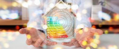 Businessman using 3D rendering energy rating chart in a wooden h. Businessman on blurred background using 3D rendering energy rating chart in a wooden house Stock Photos