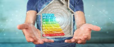 Businessman using 3D rendering energy rating chart in a wooden h. Businessman on blurred background using 3D rendering energy rating chart in a wooden house Stock Photo