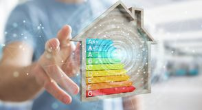 Businessman using 3D rendering energy rating chart in a wooden h. Businessman on blurred background using 3D rendering energy rating chart in a wooden house Royalty Free Stock Photos