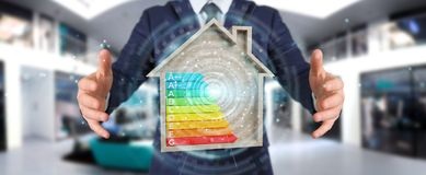 Businessman using 3D rendering energy rating chart in a wooden h. Businessman on blurred background using 3D rendering energy rating chart in a wooden house Royalty Free Stock Photography