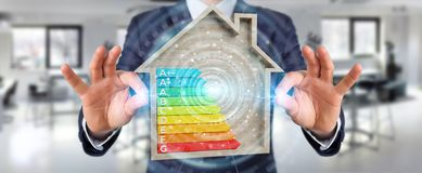 Businessman using 3D rendering energy rating chart in a wooden h. Businessman on blurred background using 3D rendering energy rating chart in a wooden house Royalty Free Stock Images