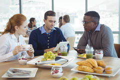 Businessman using digital table while sitting with colleagues in cafeteria. Businessman using digital table while sitting with colleagues at breakfast table in Stock Images