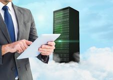Businessman using digital tablet against background with server building in sky Royalty Free Stock Photos