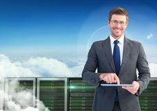 Businessman using digital tablet against database server systems in sky Stock Images