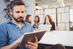 Businessman using digital tablet against female coworkers Stock Photos
