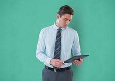 Businessman using digital tablet against green background Stock Photos