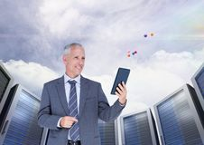 Businessman using digital tablet against server systems in sky Royalty Free Stock Images