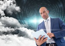 Businessman using digital tablet with binary codes and cloud in background Stock Images