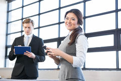 Businessman using digital tablet and businesswoman using mobile phone Stock Image