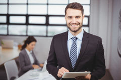 Businessman using digital tablet while colleague in background Royalty Free Stock Images