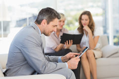 Businessman using digital tablet with colleagues behind Royalty Free Stock Images