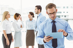 Businessman using digital tablet with colleagues behind Stock Photos