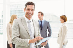 Businessman using digital tablet with colleagues behind Royalty Free Stock Photo