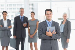 Businessman using digital tablet with colleagues behind Stock Image