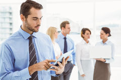 Businessman using digital tablet with colleagues behind Stock Photography