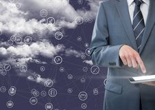 Businessman using digital tablet with connecting icons against blue background with clouds. Close-up of businessman using digital tablet with connecting icons Royalty Free Stock Photography
