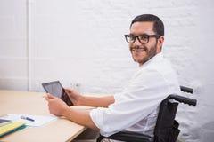 Businessman using digital tablet at desk Stock Photo
