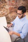 Businessman using digital tablet at desk Stock Photography