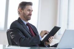 Businessman Using Digital Tablet At Desk Stock Photos