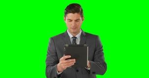 Businessman using digital tablet. On green background stock video