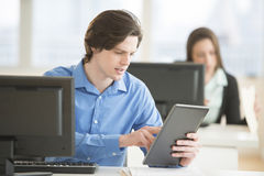 Businessman Using Digital Tablet At Office Desk. Young businessman using digital tablet at desk in office Stock Photos