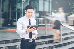 Businessman using a digital tablet office outdoors and Blurred P. Eople Walking in Front of Modern Office Building Stock Images