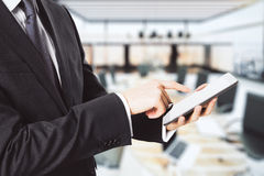 Businessman using digital tablet at office space background Stock Images