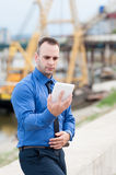 Businessman using digital tablet outdoor. Construction site behind him Royalty Free Stock Images