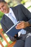 Businessman using digital tablet in park Royalty Free Stock Image