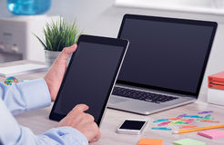 Businessman using ipad digital tablet pc and macbook laptop on the office desk. Businessman holding and working with ipad digital tablet pc. Modern office desk Royalty Free Stock Image