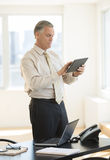 Businessman Using Digital Tablet While Standing By Desk Stock Image