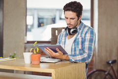 Businessman using digital tablet while standing by table in office Royalty Free Stock Photos